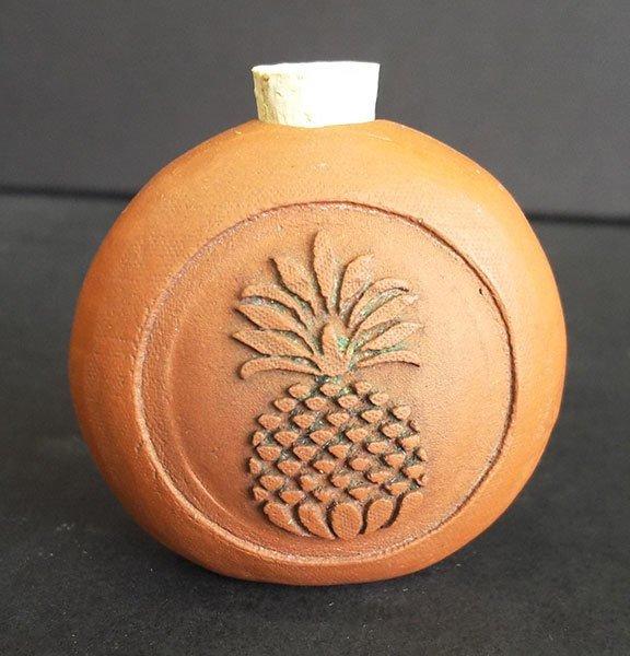 Terracotta bottle embossed with pineapple design