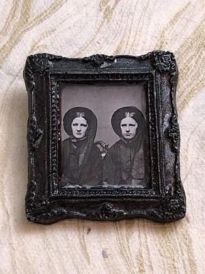 frame brooch (two women)
