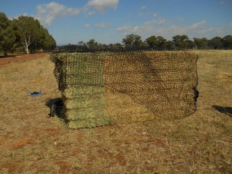 Then walk around the bale letting the netting drop to the ground so that the drawstring is at the base