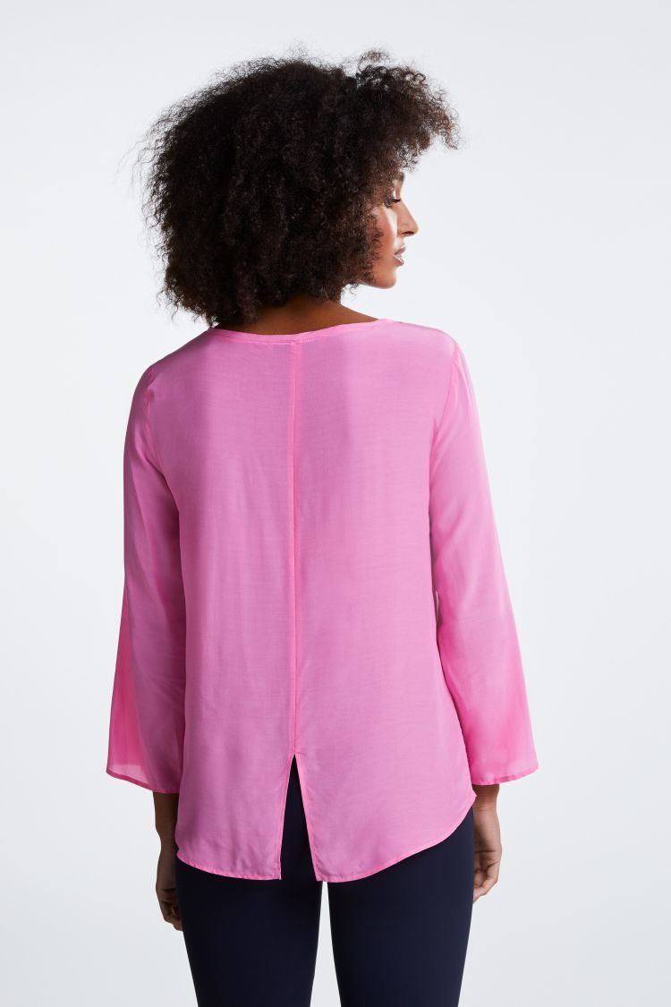Bright pink top with 3/4 sleeves and dipped hem