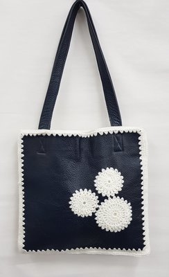 Blauwe tas met witte geborduurde bloemen