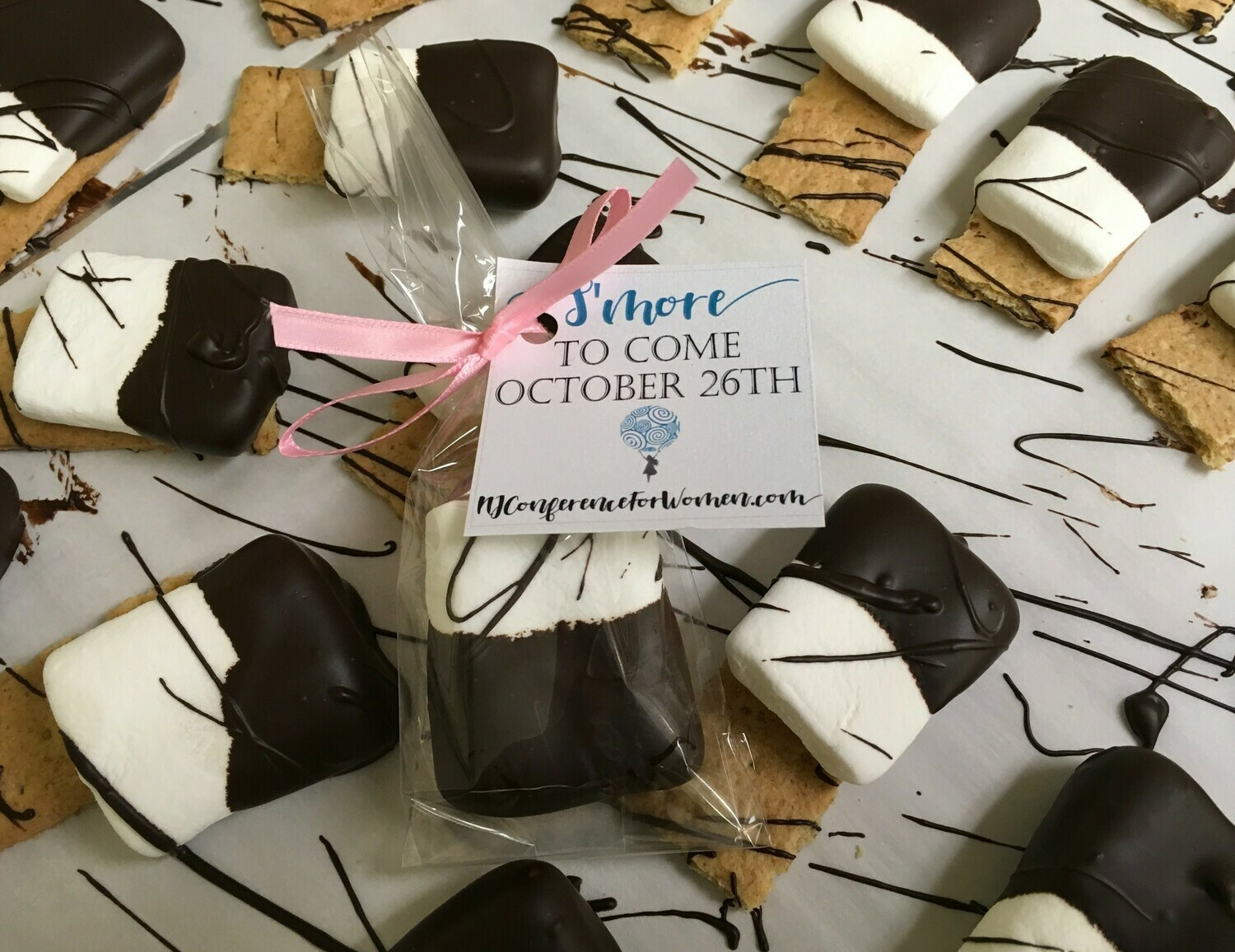 Smore's Favor for any Occassion!  Your choice of ribbon.  Flat Marshmallow covered in Dark Chocolate on a Graham. Tag is extra $12.00 per 25 or bring us your own tag and we will attach it no charge.