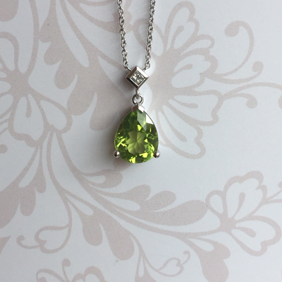 9ct white gold peridot and diamond pendant, suspended upon a 9ct white gold chain