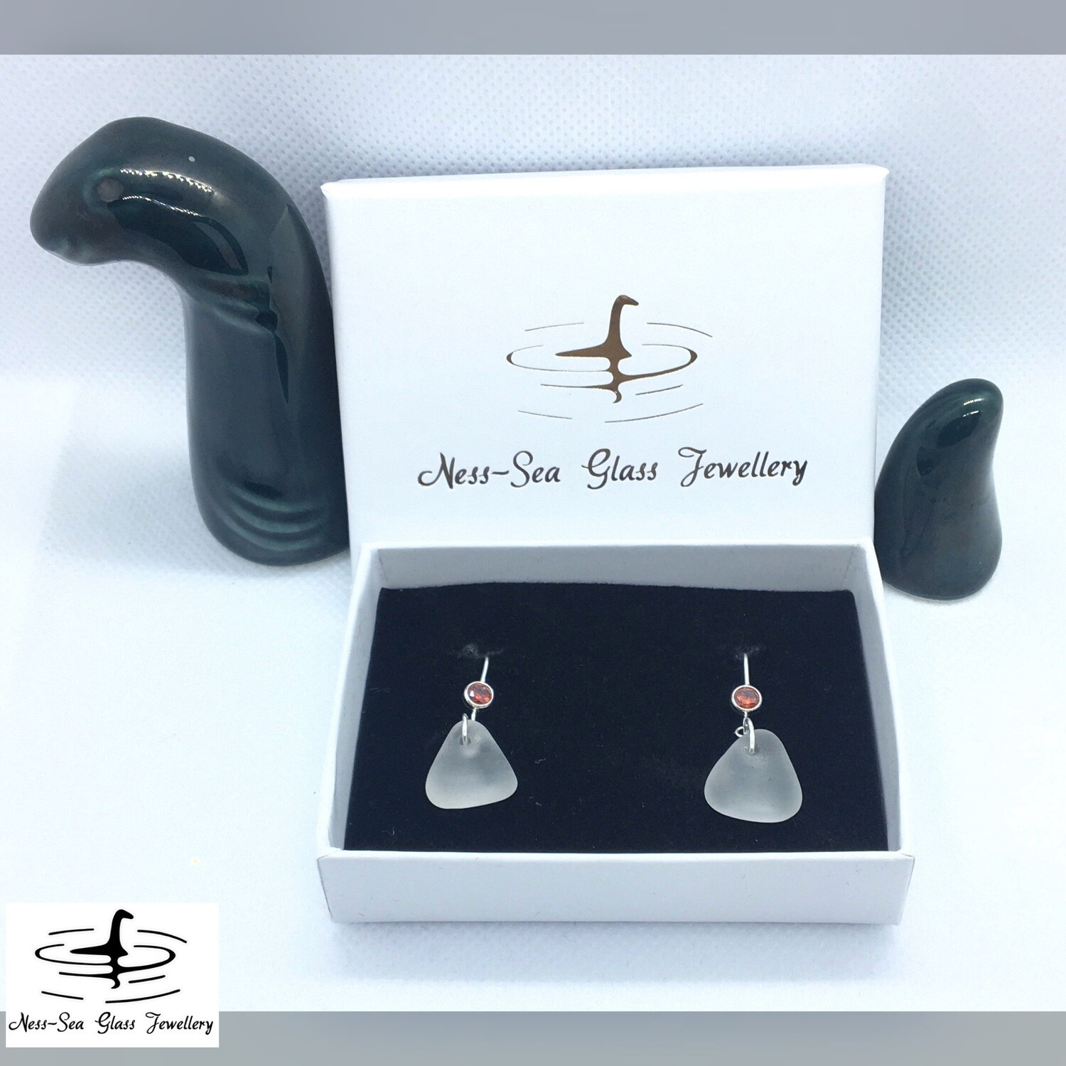 Clear Loch Ness Sea Glass Sterling Silver Hook Earrings with Red Cubic Zirconia Gemstone Detail.