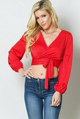 This top features a v neck, surplice, long puff sleeve, cropped length, wrap around tie, and body fit.
