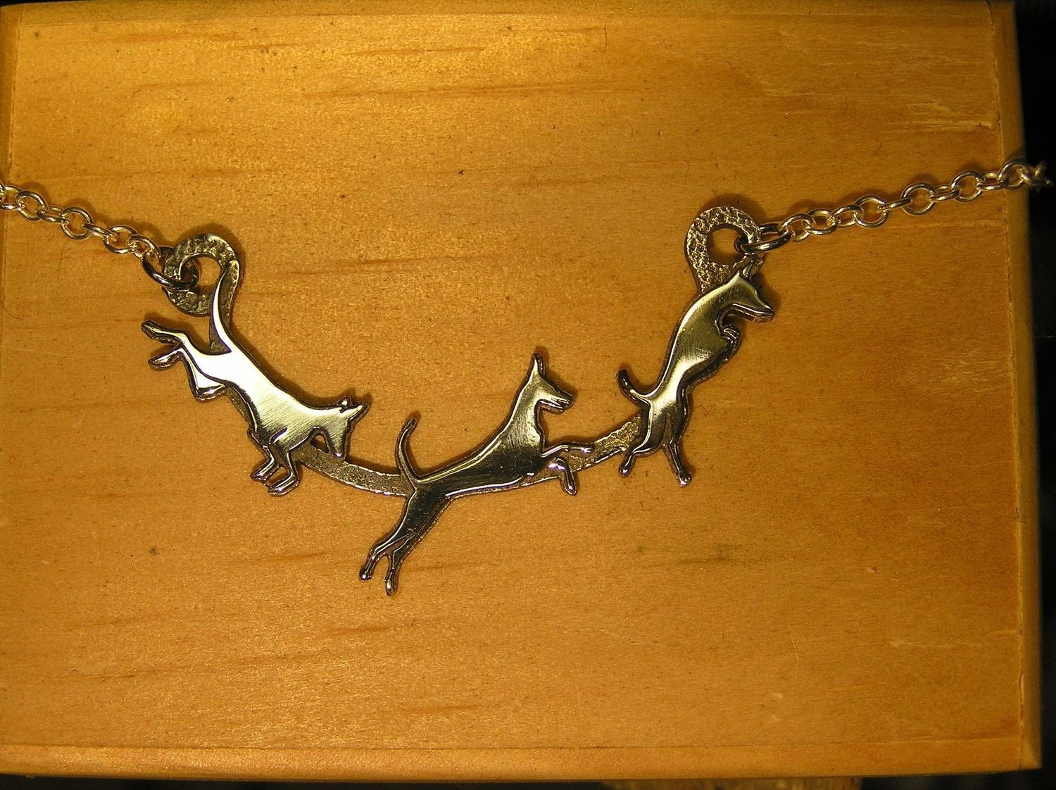 Leaping dogs on a silver chain