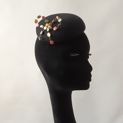 Black pillbox with beaded bow on gold coated wire