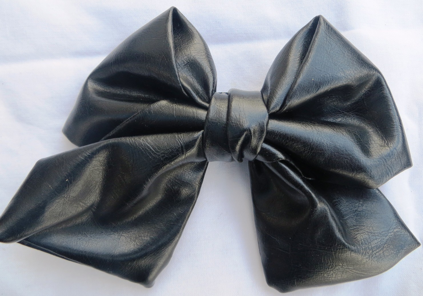 Black faux leather metallic look bow