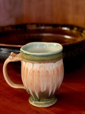 Footed handmade ceramic mug in greens and yellows.