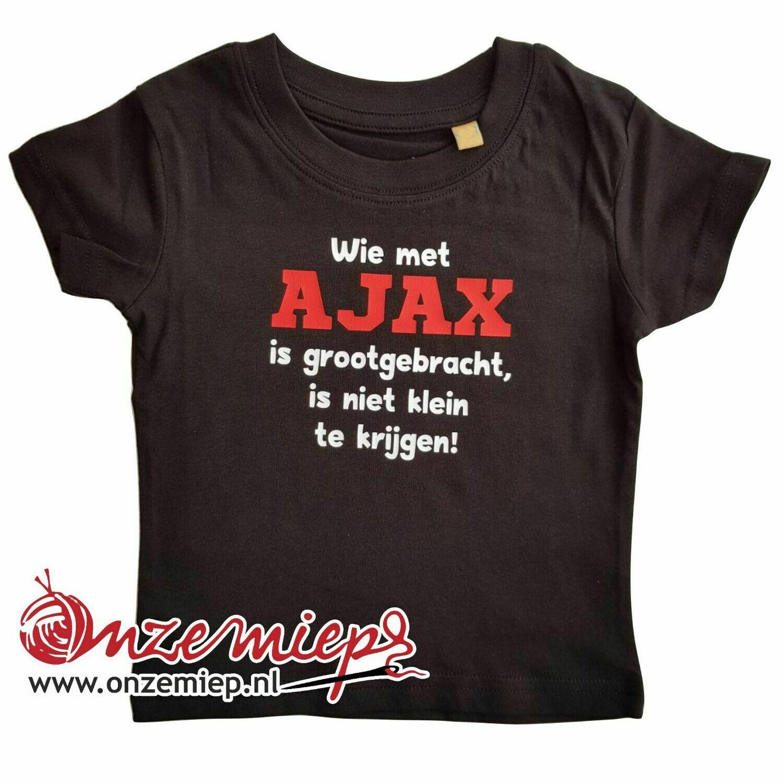 """Zwart baby shirt met """"Wie met AJAX is grootgebracht, is niet klein te krijgen"""""""