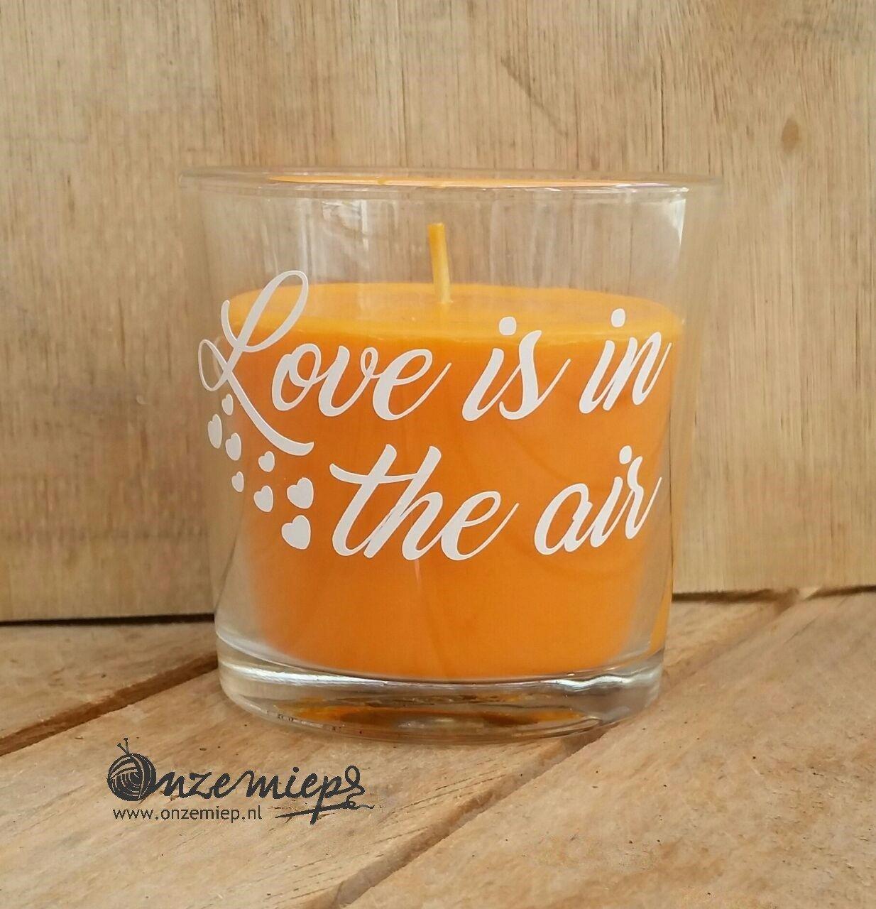 """Oranje geurkaars met de tekst """"Love is in the air"""""""