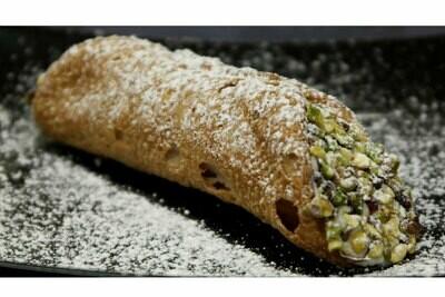 Cannolo siciliano ripieno di ricotta e guarnito con granella di pistacchio