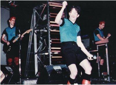 Devo / On Stage, Mark in Center, Blue-Black Shirts | Photo Print (1981)