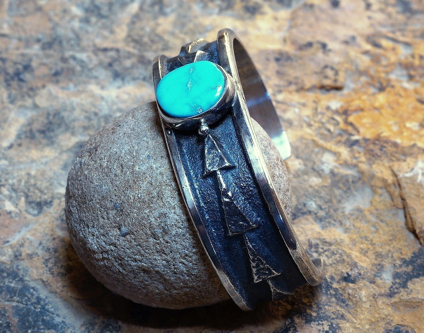 The Sleeping Beauty arrow bracelet laying on a rock showcasing the small arrow engravings on the side and the turquoise in the middle