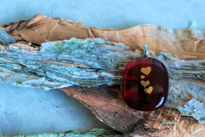 Beautiful red glass with gold hearts on this fused glass pendant.