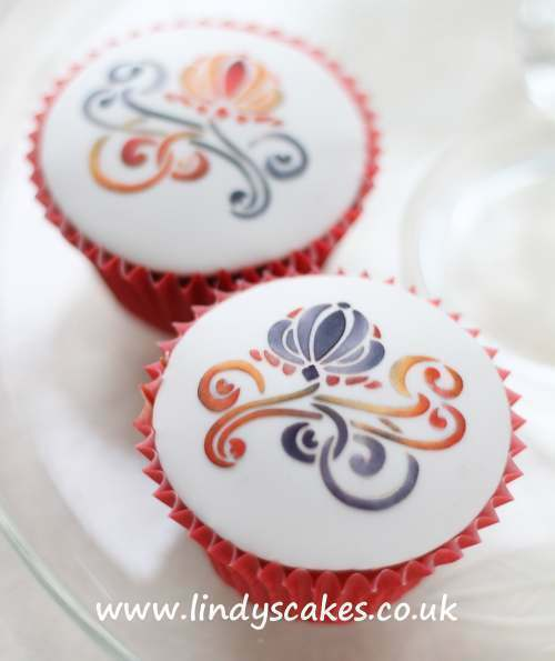 orange and black Art Nouveau flower stencil design on cupcakes by Lindy Smith