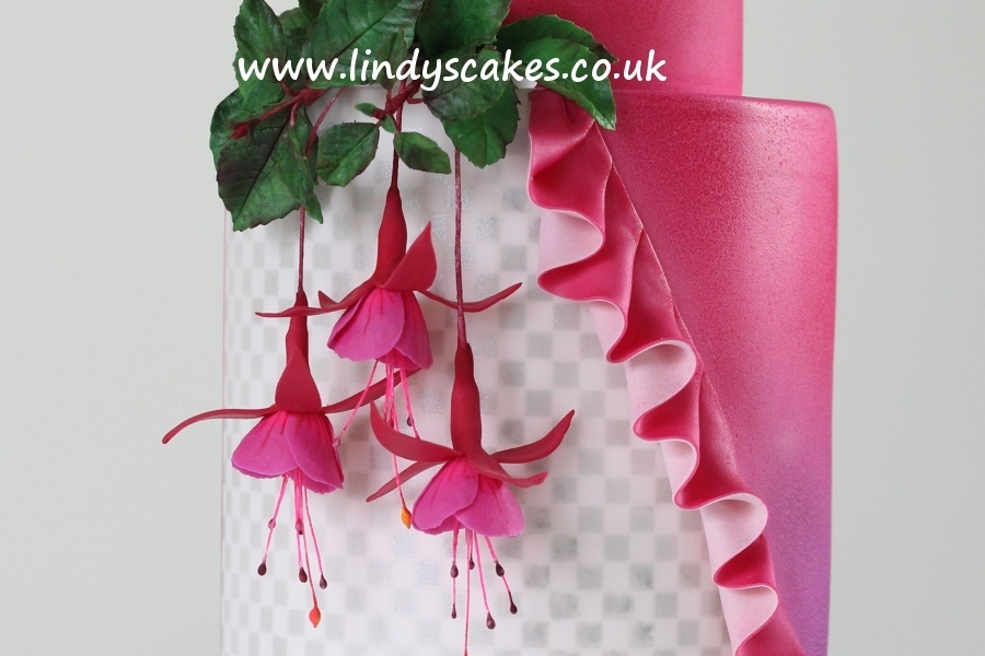 Beautiful life-like sugar fuchsias hanging down the sides of a wedding cake