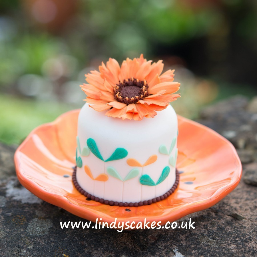 sugar marigold flower tops a mini cake beuatifully