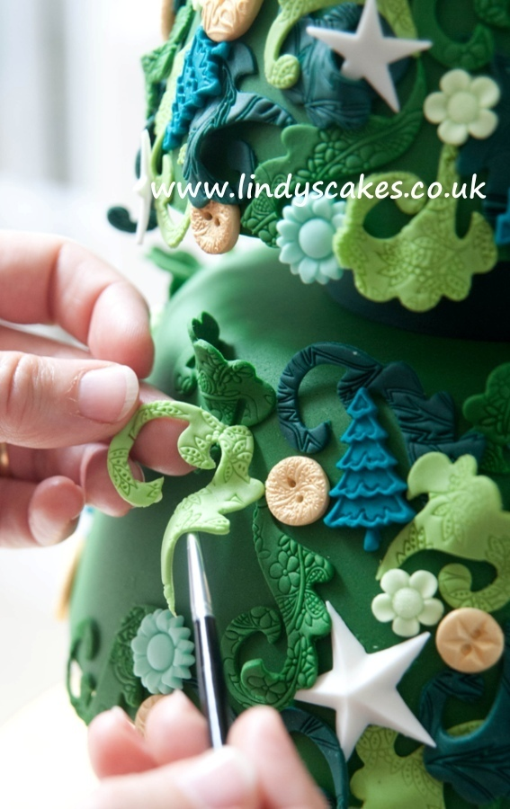 Close up of adding the scrolls to Lindy's  Christmas tree cake from 'Creative Colour for Cake Decorating'