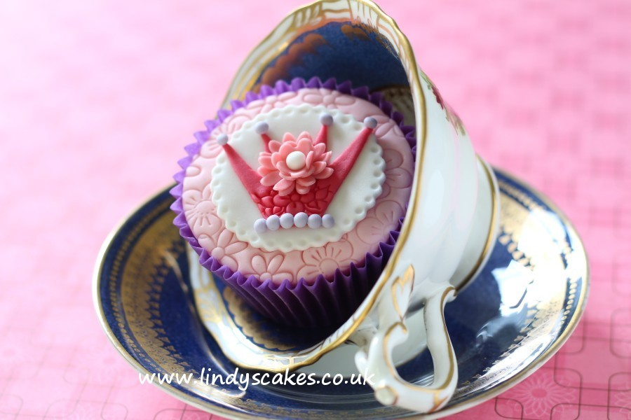Beautifully detailed crown decorates the top of this pretty pink princess cupcake displayed in a teacup