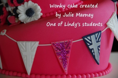 Lindy's bunting cutter used to create a string of bunting to  attractively decorate the side of this striking pink cake