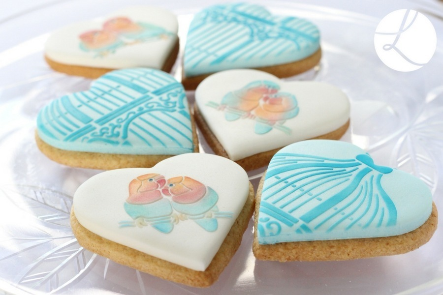 Lindy's lovebird stencil used on  heart shaped cookies in pastel peach and aqua