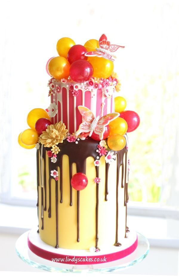 Large butterfly cutter used to decorate this pink and yellow chocolate drip cake by Lindy Smith