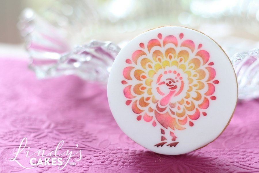 Pink peacock stencilled onto a sugarpaste covered biscuit