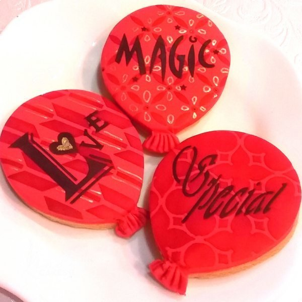 Balloon cookies - one decorated with the retro arrow cake stencil cm004