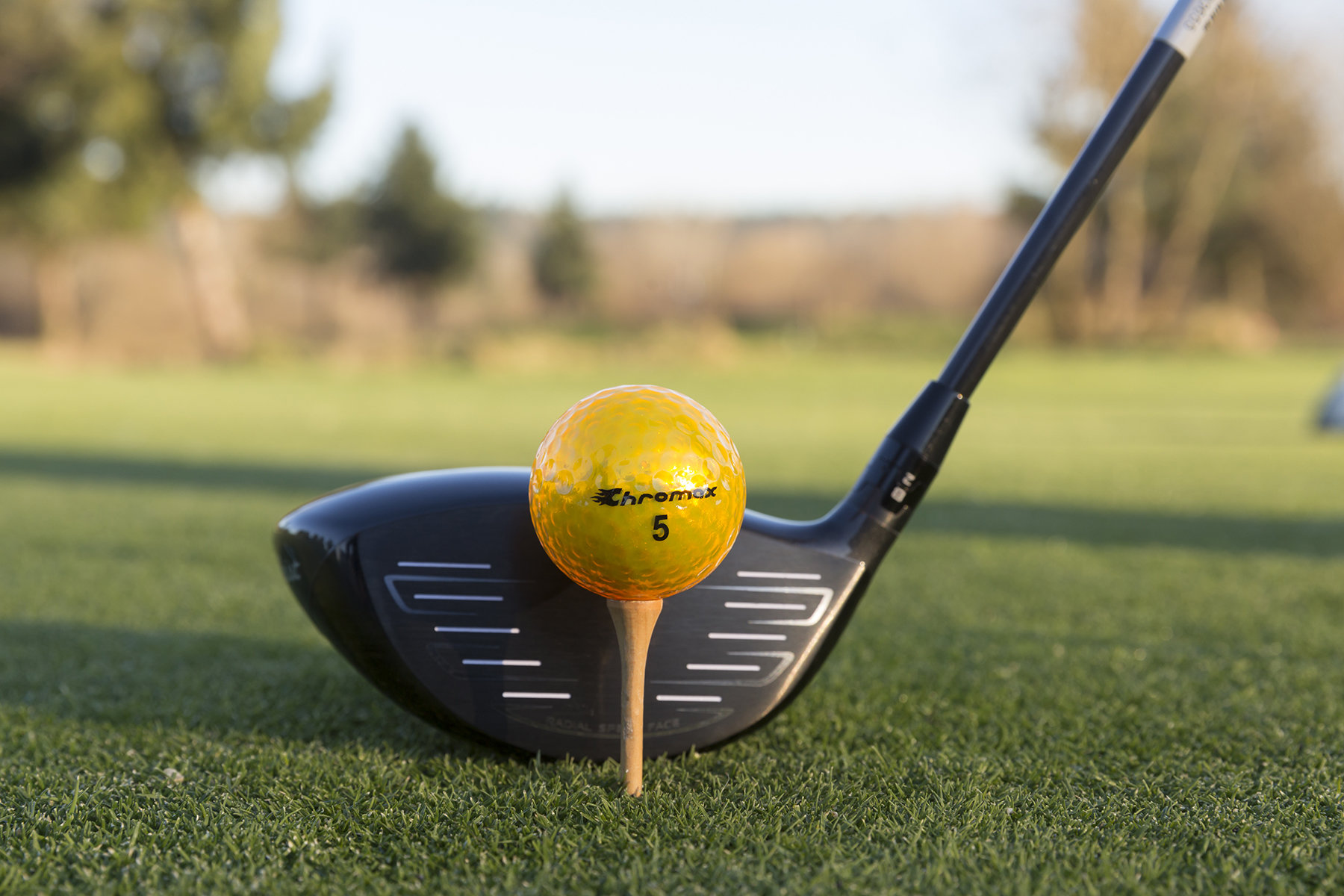 Chromax gold golf ball with driver